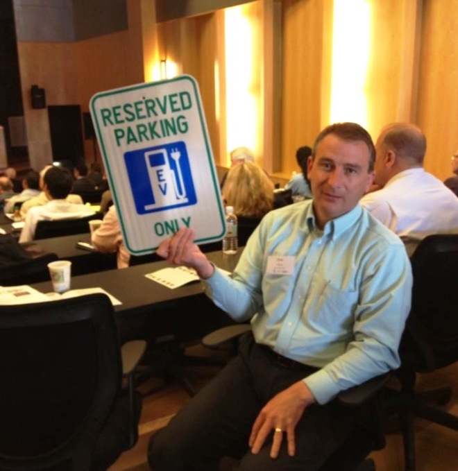 Don Grice, Deputy DPW Director holds up the Michigan regulatory sign for EVs