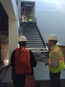 Workers finishing cement on a major stairway in the office area of the building