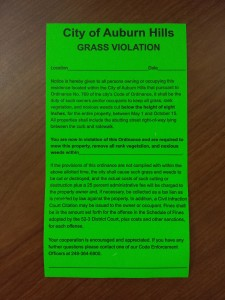 Grass Violation stickers are posted on or near the front door of residential properties
